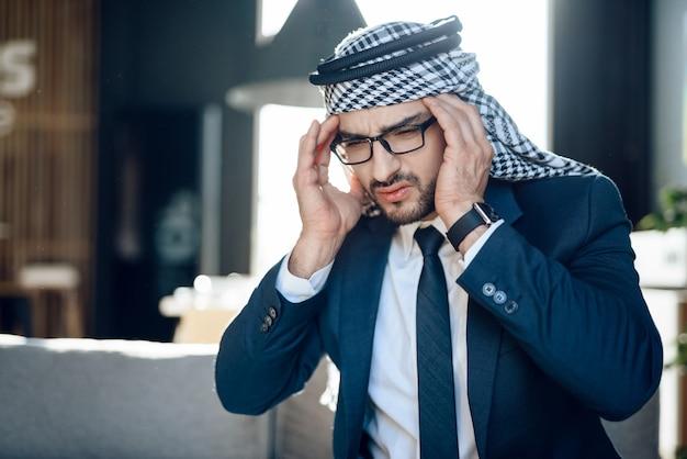 Feche acima da foto do árabe tem fortes dores de cabeça
