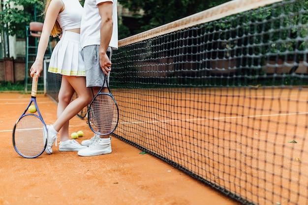 Feche acima da foto dos pés dos pares na corte de tênis que guarda sobre a raquete das mãos.