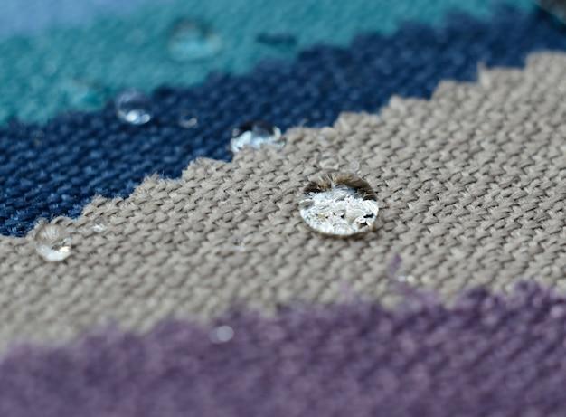 Feche acima da gota da água em amostras de matéria têxtil do gunny. conceito para superfícies limpas e impermeáveis