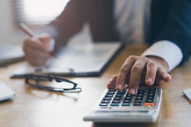Feche acima da ideia das mãos da calculadora do uso do homem de negócios calcule financeiro do negócio.