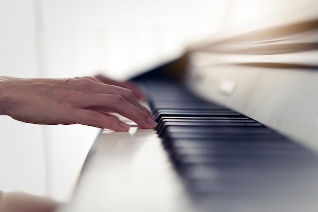 Feche acima da ideia das mãos da mulher que jogam o piano eletrônico em casa.