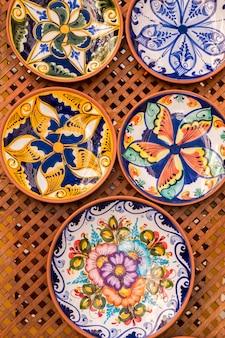 Feche acima da ideia de pratos pintados à mão bonitos em uma loja.