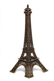 Feche acima da ideia de uma estátua pequena da torre eiffel isolada em um fundo branco.