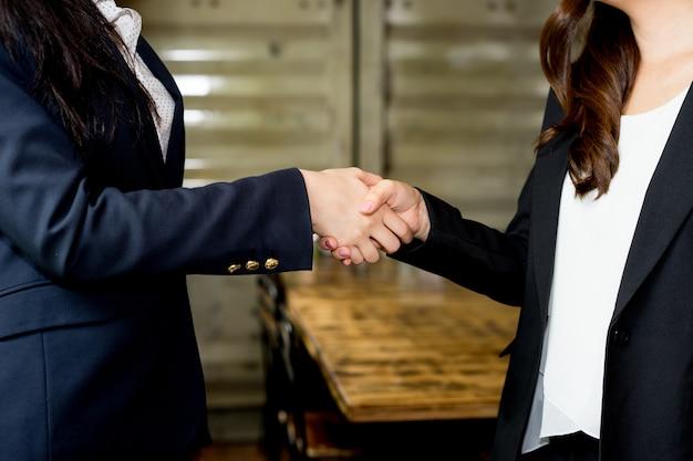 Feche acima da ideia do handshake da parceria do negócio, processo do aperto de mão de duas mulheres de negócio.
