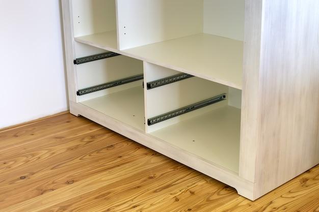 Feche acima da instalação da gaveta de madeira no armário contemporâneo.