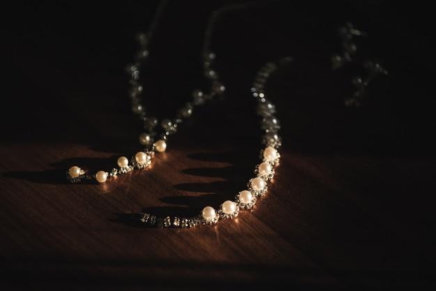 Feche acima da joia do casamento no fundo de madeira. colar de pérolas e brincos
