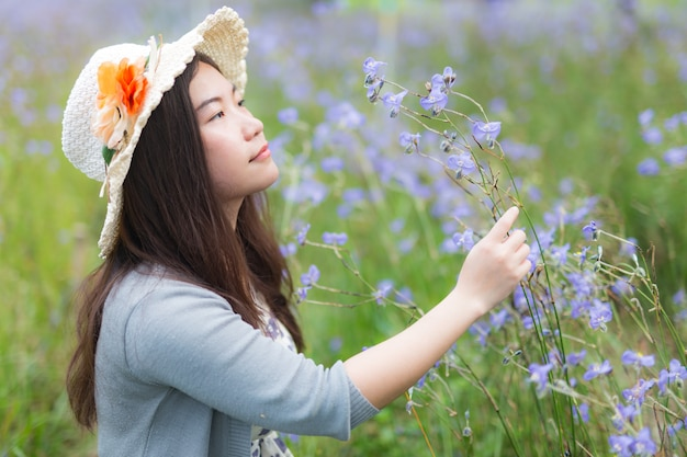 Feche acima da jovem mulher asiática bonita com gigante murdannia doce, flores violetas tailandesas, no campo do gigantedan de murdannia.