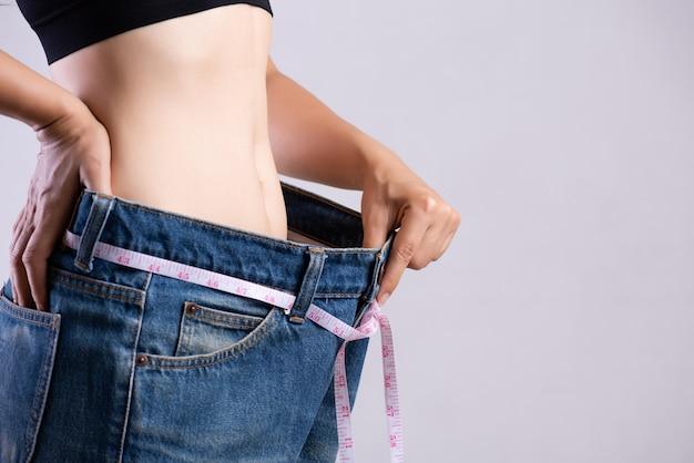 Feche acima da jovem mulher magro que mede sua cintura fina com uma fita métrica.
