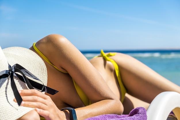 Feche acima da jovem mulher quadril e ombro que coloca na cadeira de praia no banho de sol da costa de mar.