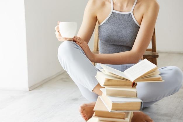 Feche acima da jovem mulher que guarda a xícara de café do livro que senta-se no assoalho com os livros sobre a parede branca cedo na manhã.