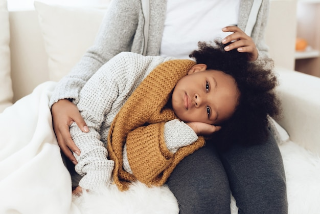 Feche acima da mãe afro-americano com criança doente.