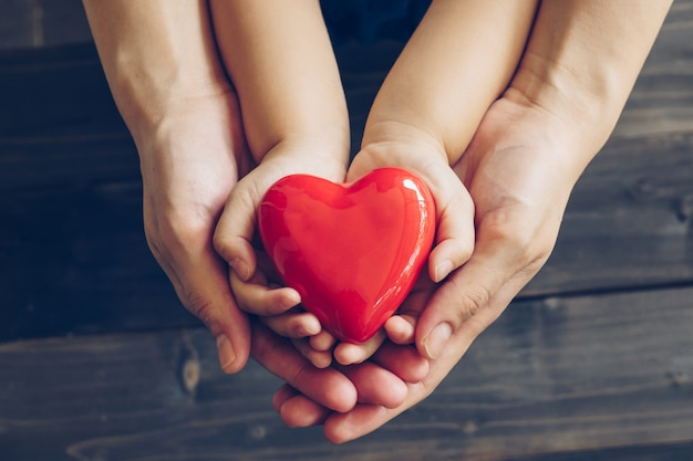 Feche acima da mãe e das mãos das crianças que dão o coração vermelho no fundo de madeira