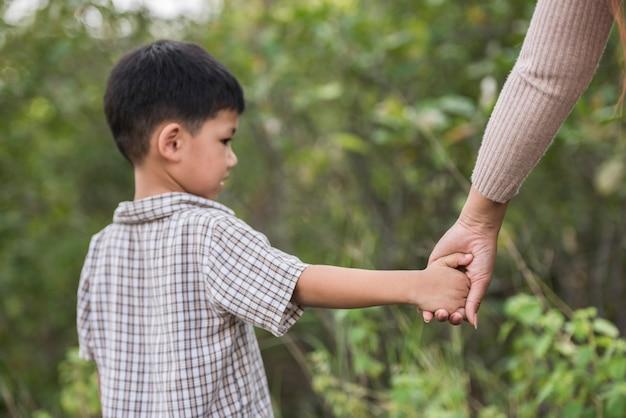 Feche acima da mamã feliz e do filho que guardam a mão em um parque. conceito de família.