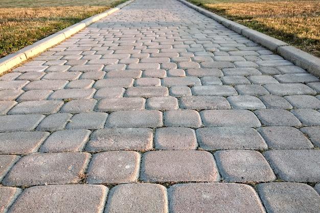 Feche acima da maneira do caminho pavimentado pedra da laje