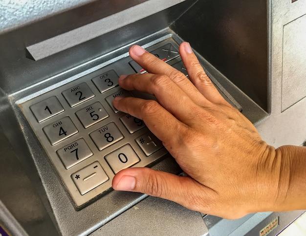 Feche acima da mão a pressionar a chave numérica na máquina atm.