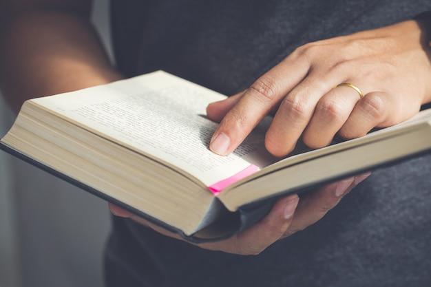 Feche acima da mão abra a bíblia, leituras de domingo, bíblia