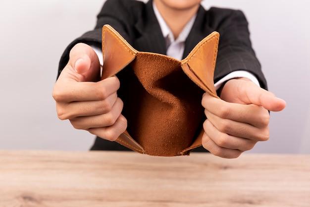 Feche acima da mão abre uma carteira vazia no fundo de madeira.