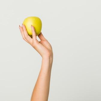 Feche acima da mão da jovem mulher hispânica, segurando uma maçã