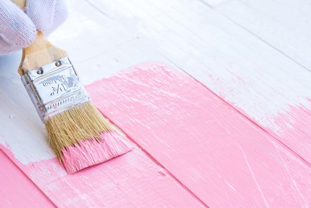 Feche acima da mão da mulher que guarda a escova que pinta a cor cor-de-rosa em uma tabela de madeira branca.