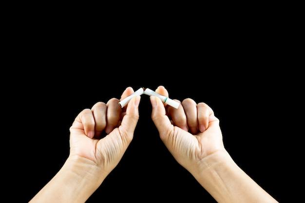 Feche acima da mão da mulher que quebra, esmagando ou destruindo cigarros no fundo preto.