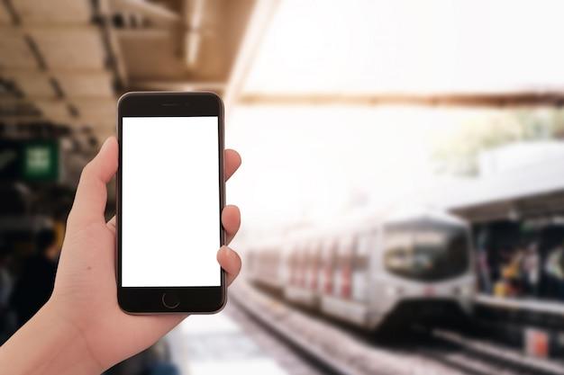 Feche acima da mão da mulher usando um telefone esperto com a tela vazia no estação de caminhos-de-ferro de hong kong.