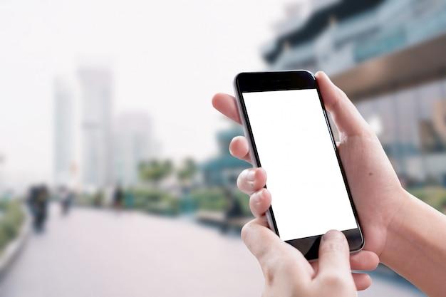 Feche acima da mão da mulher usando um telefone esperto com a tela vazia no shopping.
