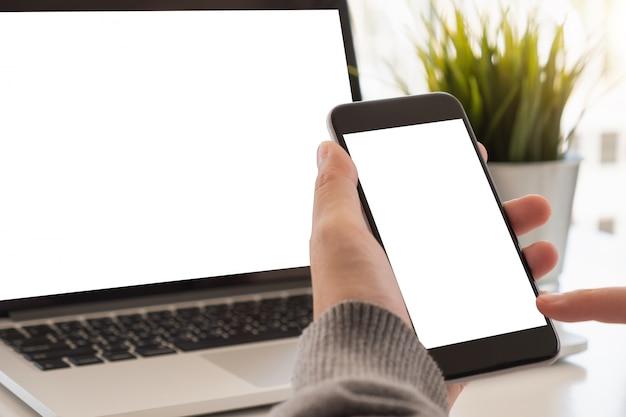 Feche acima da mão da mulher usando um telefone esperto com tela vazia em casa.