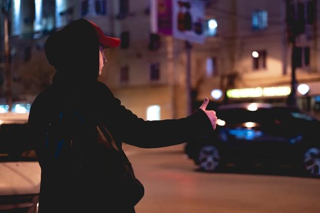 Feche acima da mão da pessoa que viaja e que espera um suporte de carro em uma estrada na noite