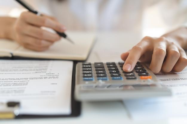 Feche acima da mão da vista do equilíbrio de renda calculador da pessoa.