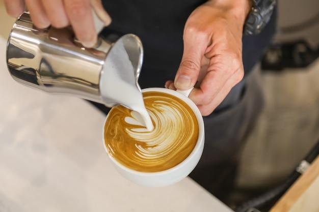 Feche acima da mão do barista que derrama o leite forçado na xícara branca do café quente para criar a arte do café com leite.