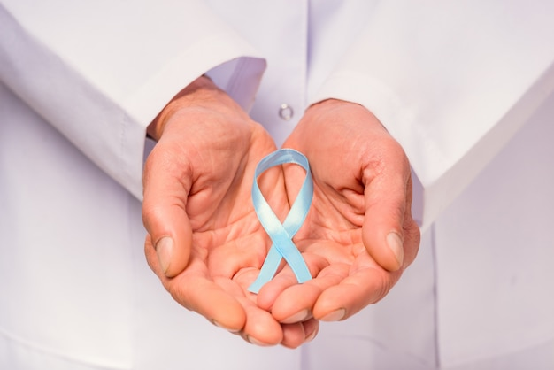 Feche acima da mão do doutor com uma fita azul.