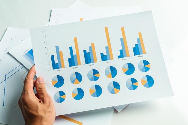 Feche acima da mão do homem de negócio com análise financeira da contabilidade do relatório.