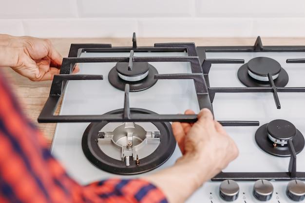 Feche acima da mão do homem instale o fogão de ongas do queimador no kithen. reparos do painel de controle de gás