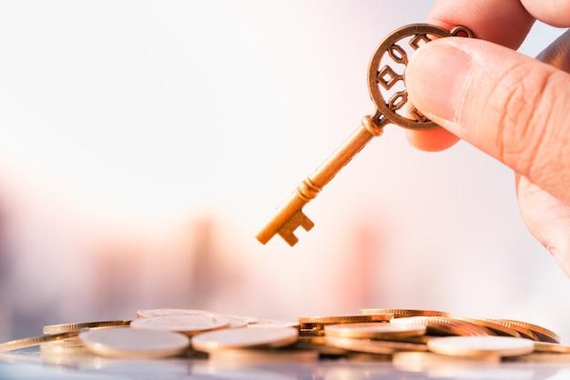 Feche acima da mão do homem que guarda chave na pilha da moeda com arquitectura da cidade como fundos.