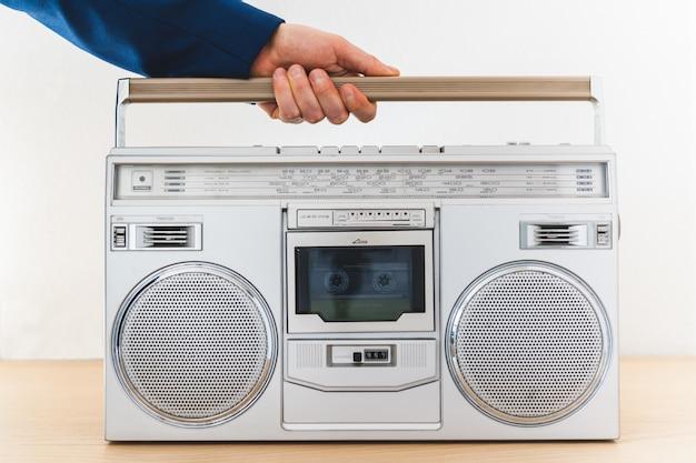 Feche acima da mão do homem que guarda um rádio velho dentro de casa.