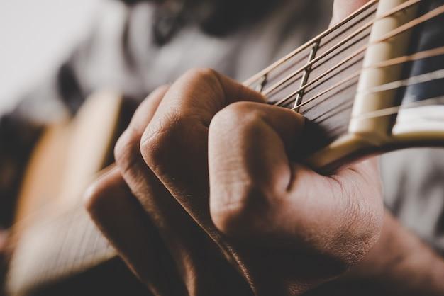 Feche acima da mão do homem que joga a guitarra.