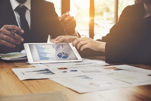 Feche acima da mão dos povos do negócio que aponta no original de negócio na tabuleta digital durante a discussão na reunião. grupo de apoio e conceito de reunião.