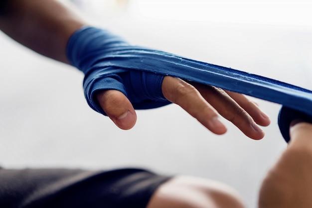 Feche acima da mão masculina do pugilista com as ataduras azuis do encaixotamento.