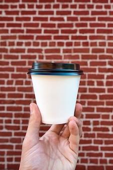Feche acima da mão masculina que guarda a xícara de café do livro branco, contra uma parede de tijolo vermelho. aproveitando o café para ir