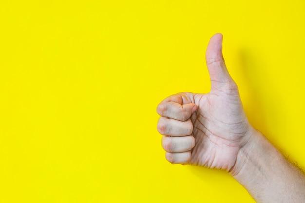 Feche acima da mão masculina que mostra os polegares acima do sinal sobre o amarelo