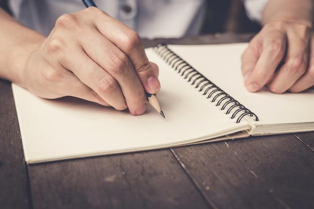 Feche acima da mão, mulher, escrevendo caderno no fundo da mesa de madeira.