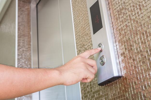 Feche acima da mão, pressionando o botão elevador de prata