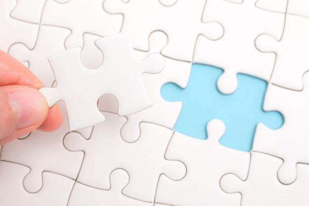 Feche acima da mão que coloca a última parte do enigma de serra de vaivém conceptual da resolução de problemas, encontrando uma solução.