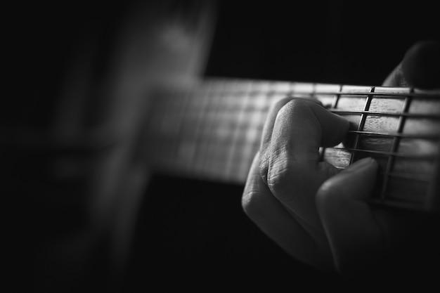 Feche acima da mão que joga a guitarra acústica no fundo da memória.