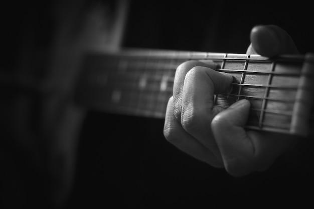 Feche acima da mão que joga o fundo da guitarra acústica.
