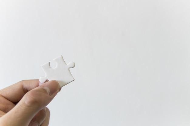 Feche acima da mão segurando jigsaw branco no espaço da cópia de fundo branco
