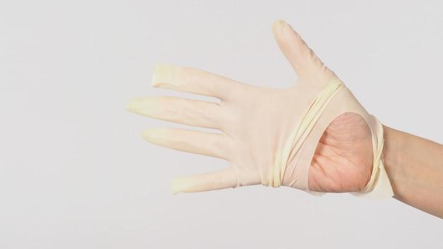 Feche acima da mão usando luvas médicas rasgadas ou luvas de borracha rasgadas em fundo branco.
