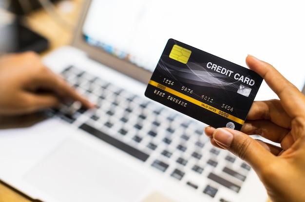 Feche acima da mão usando o cartão de crédito que compra em linha, conceito cashless