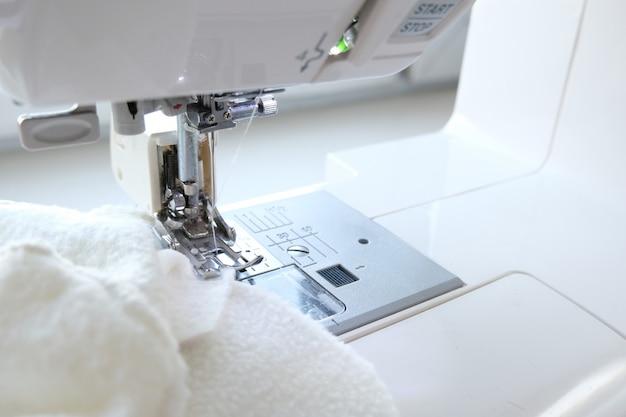 Feche acima da máquina de costura com matéria têxtil branca da tela no local de trabalho. costurar processo. - bordado, artesanato, costura e alfaiataria conceito.