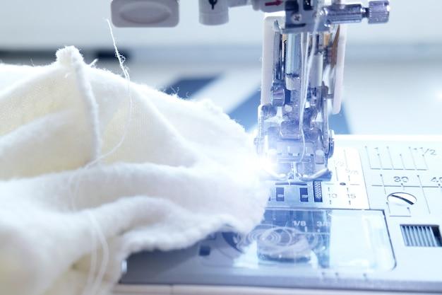 Feche acima da máquina de costura com tecido branco têxtil no local de trabalho